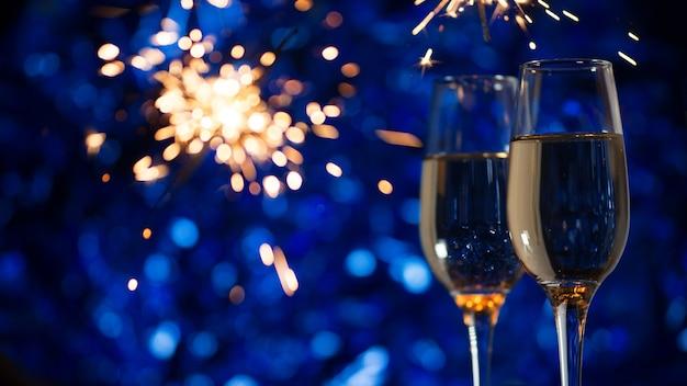 Bicchieri di champagne su una festosa decorazione blu con fuochi d'artificio Foto Premium