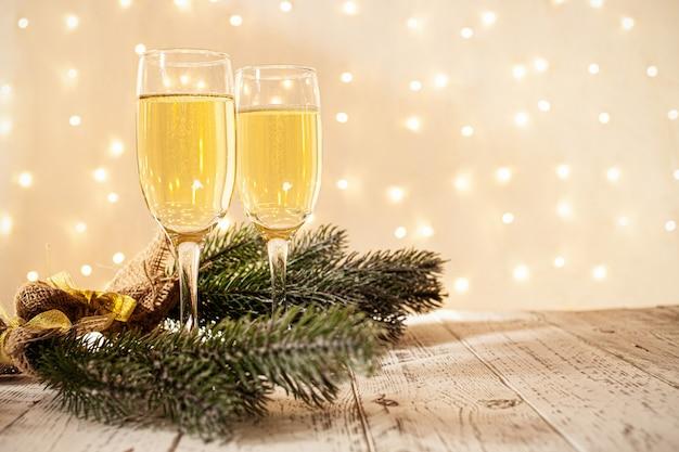 Bicchieri di champagne su un tavolo di legno con una ghirlanda dorata sfocata, concetto di capodanno Foto Premium
