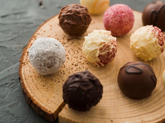 Caramelle di cioccolato smaltato su piatto di legno tagliato Foto Premium