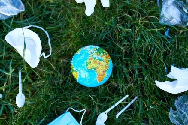 Un globo in un mucchio di immondizia sparsa su uno di erba verde Foto Premium