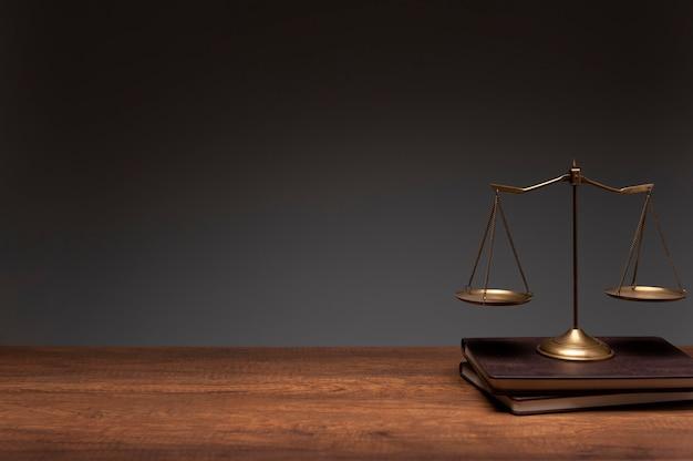 Scala dell'equilibrio dell'ottone dell'oro disposta sui libri dell'annata e sulla tabella di legno con priorità bassa grigia Foto Premium