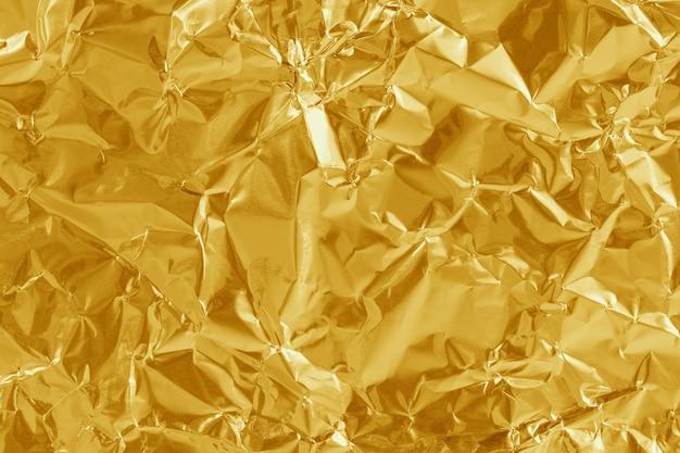 Struttura lucida foglia di lamina d'oro, carta da imballaggio gialla per lo sfondo. Foto Premium