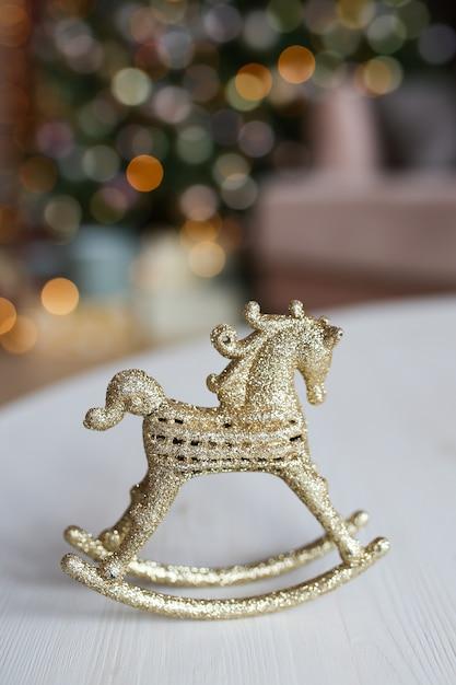 Cavallo di arredamento giocattolo d'oro in piedi sul tavolo contro lo sfondo di un albero bokeh e ghirlande Foto Premium