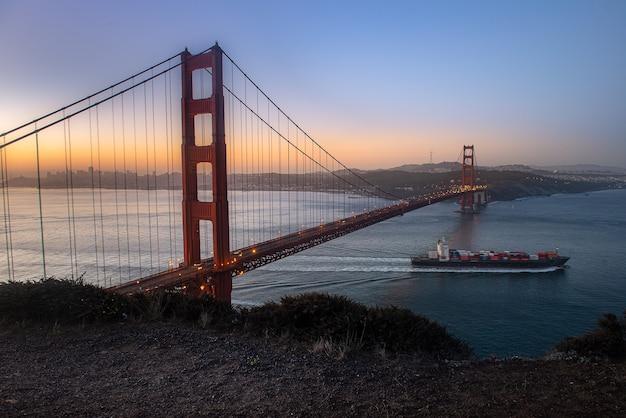 Golden gate bridge e nave da carico nella bella mattina Foto Premium