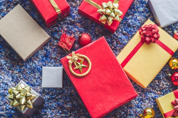 Contenitore di regalo dorato e nastro rosso sul fondo di colore Foto Premium