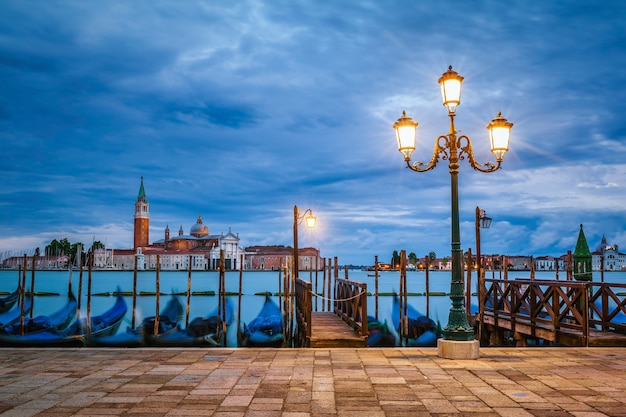 Gondole che galleggiano nel canal grande dopo il tramonto Foto Premium