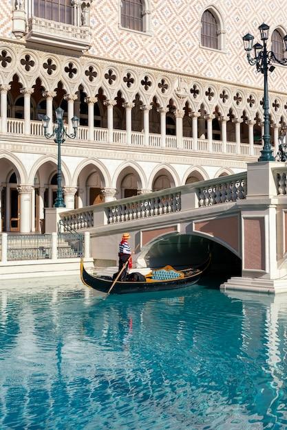 Una gondoliera al the venetian hotel and casino con un remo che galleggia su un canale su una gondola a las vegas, nevada, usa. Foto Premium