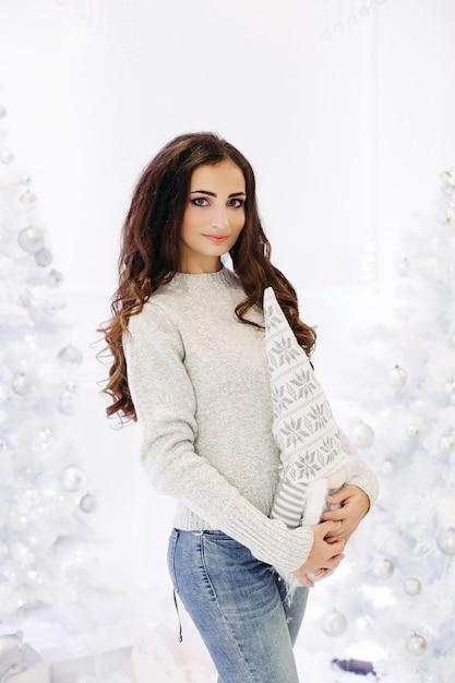 Splendida donna castana con trucco perfetto e pelle liscia che indossa un maglione grigio in posa in studio decorato per le vacanze di capodanno Foto Premium