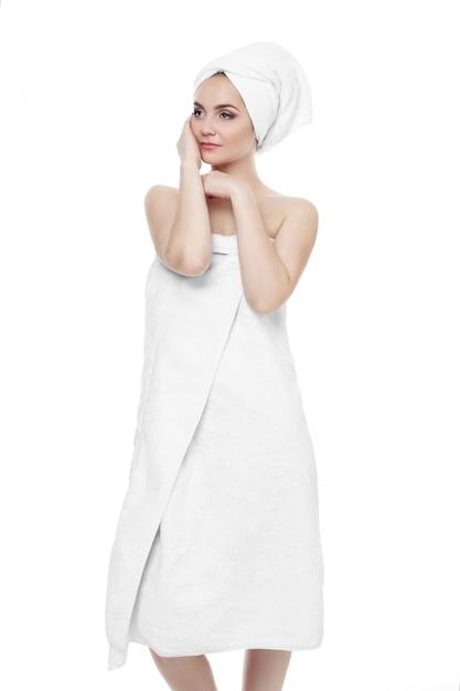 Splendida ragazza che indossa un asciugamano bianco sulla testa, tenendosi per mano vicino al trucco leggero del viso Foto Premium