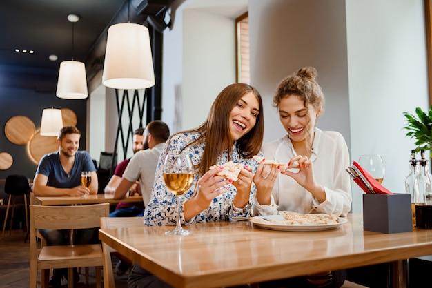 Giovani donne splendide che mangiano pizza in ristorante. Foto Premium