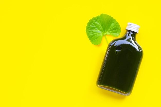 Gotu kola lascia il succo per la salute sul giallo Foto Premium