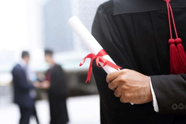 Laureato in possesso di un diploma in mano Foto Premium