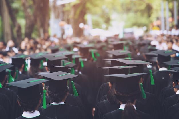 Laurea, studente tiene i cappelli in mano durante il successo di inizio laureati dell'università, congratulazioni per l'educazione del concetto.cerimonia di laurea, si congratula con i laureati all'università. Foto Premium