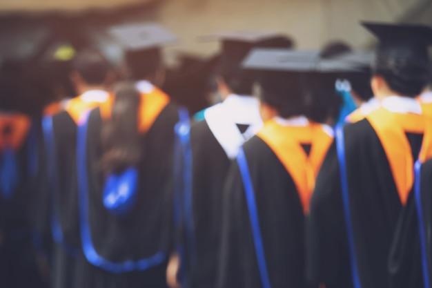 Laurea, studente tenere i cappelli in mano durante il successo di inizio laureati dell'università, congratulazioni per l'educazione del concetto Foto Premium