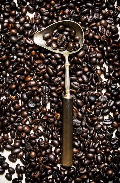 Chicco di caffè tostato in grani con un cucchiaio. Foto Premium