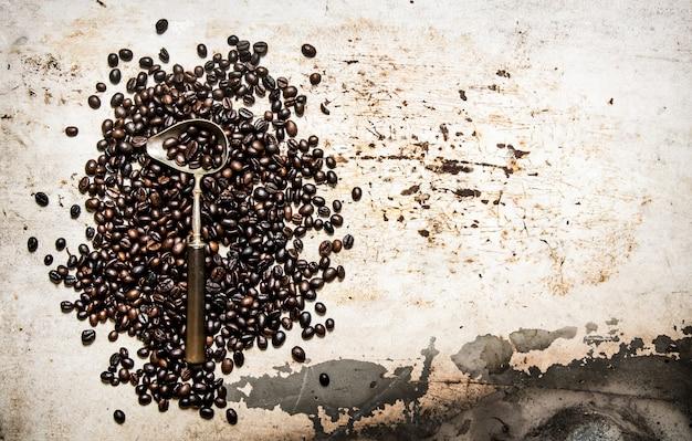 Caffè tostato in grani con un cucchiaio. su fondo rustico. Foto Premium