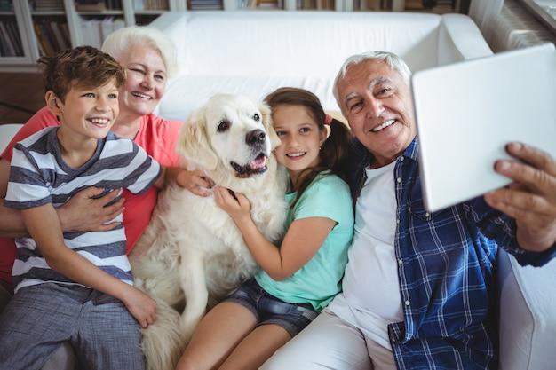 Nonni e nipoti che prendono un selfie con la compressa digitale Foto Premium