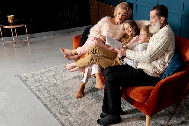 Nonni che leggono un libro con i loro nipoti con spazio di copia Foto Premium