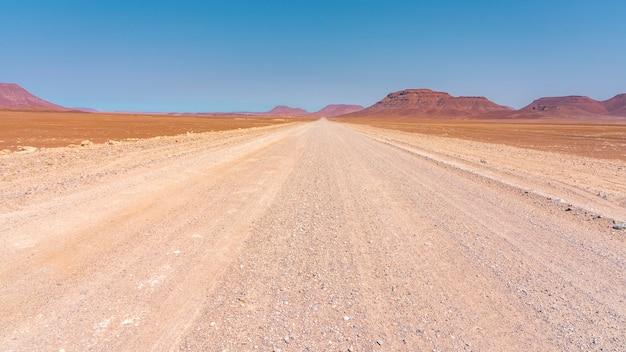 Strada della ghiaia a damaraland in namibia con le montagne rosse della roccia. da palmwag a sprinbokwasser. Foto Premium
