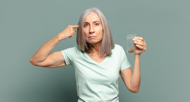 Bella donna con i capelli grigi con la marijuana Foto Premium