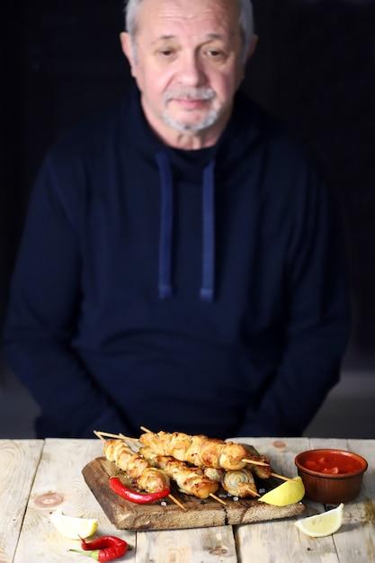 L'uomo dai capelli grigi prega prima di mangiare. Foto Premium
