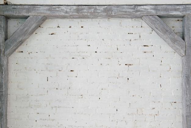 Travi in legno grigie contro un muro di mattoni bianchi. Foto Premium