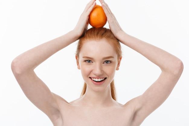 Ottimo cibo per uno stile di vita sano. bella giovane donna senza camicia che tiene pezzo di arancia che sta contro il bianco Foto Premium