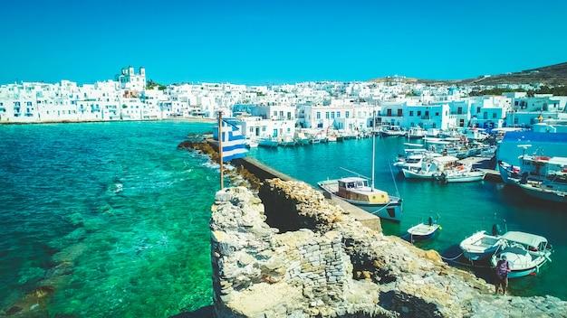 Bandiera greca sulle rovine del castello veneziano, naoussa, paros, grecia Foto Premium