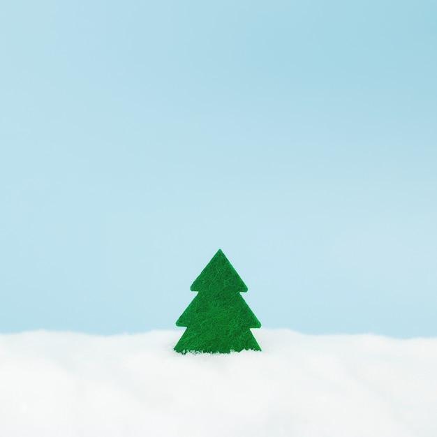 Albero di natale verde su sfondo blu con neve finta. Foto Premium