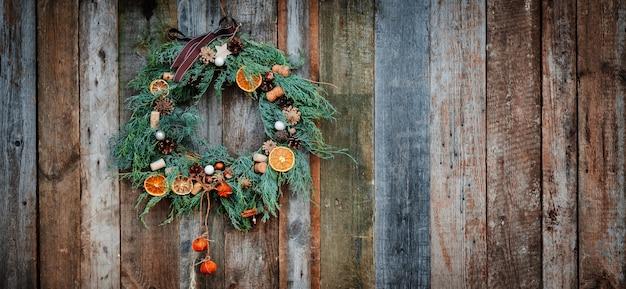 Ghirlanda di natale verde su sfondo di legno, arancia secca, sughero, abete Foto Premium