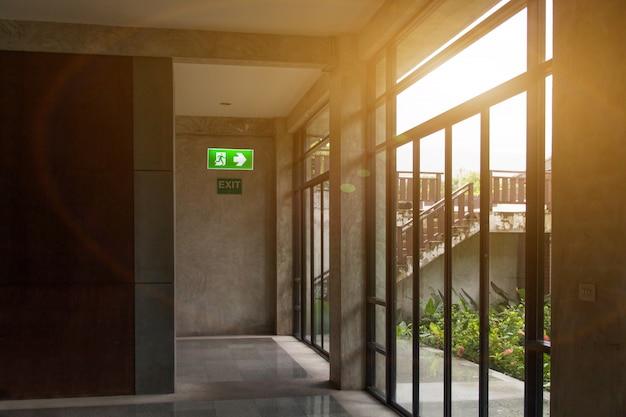 Il segnale di uscita di emergenza verde ed etichetta nessun fumo nell'angolo di sosta che mostra la via di fuga e avvisa la consapevolezza della sicurezza Foto Premium