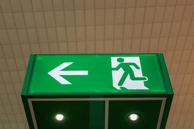 Segnale di uscita di emergenza verde che mostra la via di fuga. Foto Premium