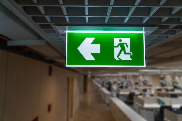 Il segno verde dell'uscita di sicurezza appende sul soffitto nell'ufficio. Foto Premium