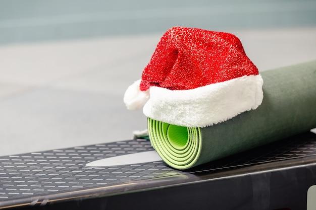 Tappetino verde con cappello di babbo natale in palestra Foto Premium