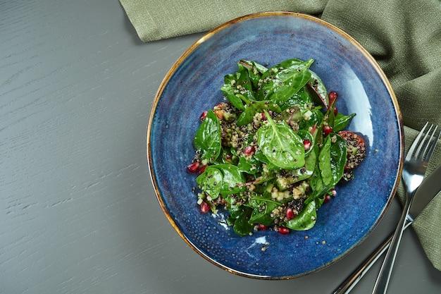 Insalata verde (spinaci) con semi di melagrana e quinoa in un piatto blu su un tavolo di legno. piatto disteso con spazio di copia. vegetariano. vista dall'alto Foto Premium