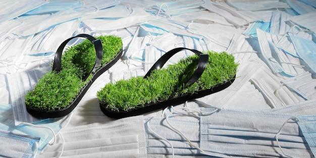 Pantofole verdi, con finta erba sulla superficie di maschere mediche che inquinano il pianeta Foto Premium