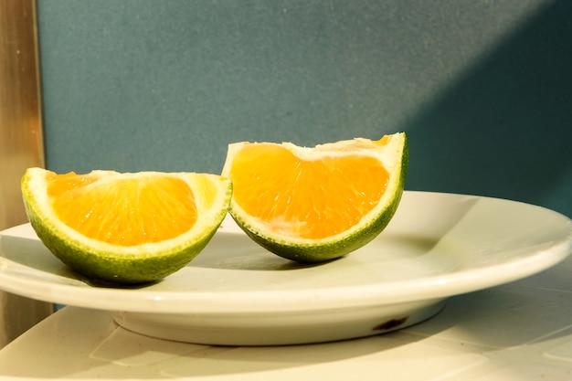 Mandarino verde tagliato a pezzi adagiato su un piatto bianco. Foto Premium