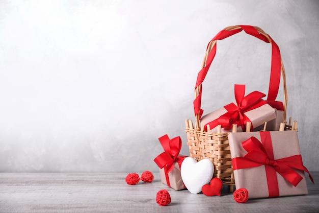 Cartolina d'auguri di san valentino con cuori e regali nel carrello su fondo di legno. con spazio per i saluti di testo Foto Premium