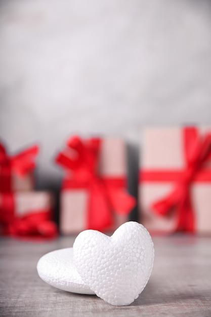 Cartolina d'auguri di san valentino con cuori su fondo in legno e regalo. con spazio per i saluti di testo Foto Premium
