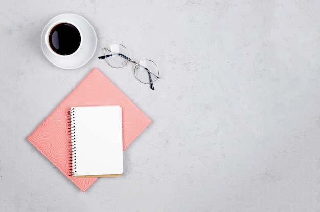 Tavolo scrivania grigio sul posto di lavoro con notebook, spazio vuoto vuoto, forniture, bicchieri e tazza di caffè. Foto Premium