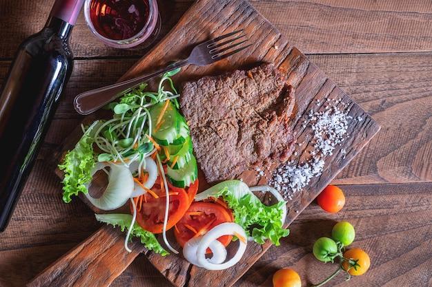 Bistecca di manzo alla griglia e sale su un tagliere di legno Foto Premium
