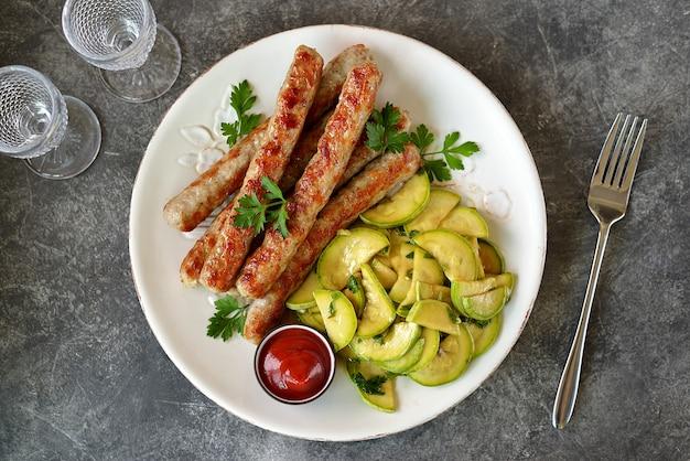 Salsicce di pollo alla griglia con insalata di zucchine Foto Premium