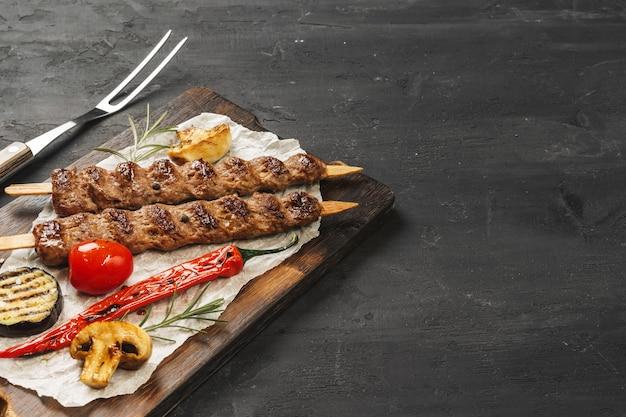 Il kebab arrostito di lula sugli spiedi è servito sul bordo di legno, tavola nera Foto Premium