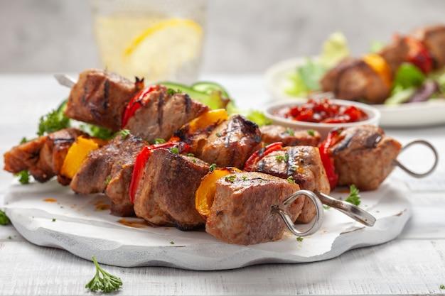 Kebab di maiale alla griglia con peperoni rossi e gialli Foto Premium