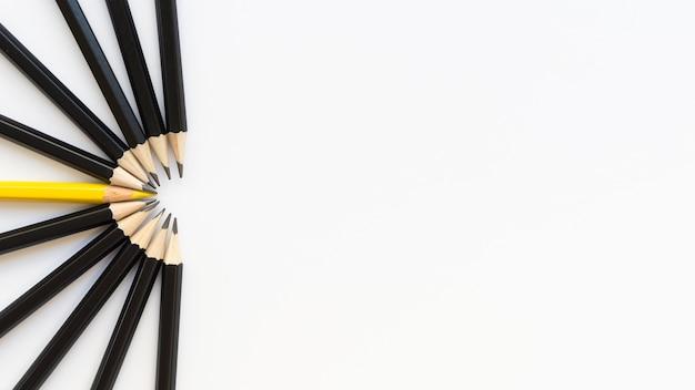 Gruppo di matite nere e una matita gialla con spazio di copia Foto Premium