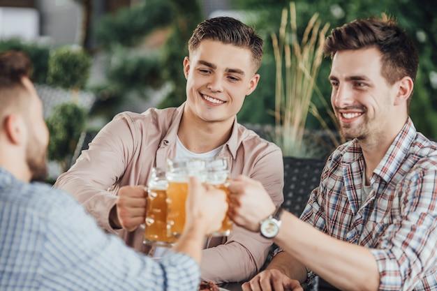 Gruppo di ragazzi che incoraggiano nella caffetteria con la birra Foto Premium