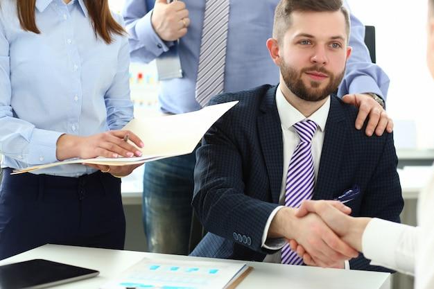 Gruppo di uomini d'affari che agitano le mani dopo una riunione produttiva Foto Premium