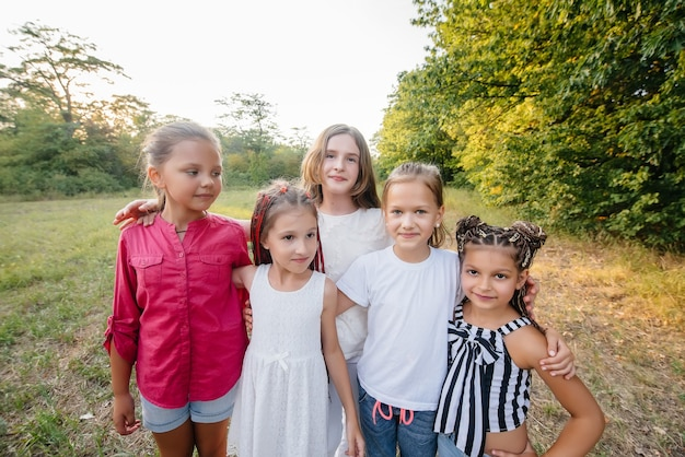 Un gruppo di ragazze allegre sorride e gioca nel parco durante il tramonto. campo estivo per bambini. Foto Premium