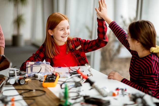 Gruppo di bambine carine che programmano giocattoli elettrici e robot in aula di robotica Foto Premium