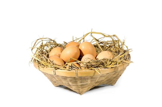 Gruppo di uova con paglia in un cesto di bambù isolato su bianco Foto Premium